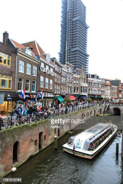 ユトレヒト、オランダ、オランダのレンガの運河の家、店や歩く人々とクルーズ船 - ユトレヒト ストックフォトと画像