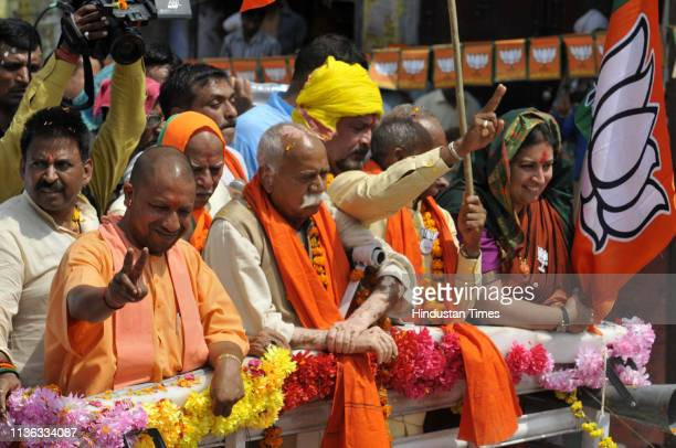 Uttar Pradesh Chief Minister Yogi Adityanath and Union Minister Smriti Irani wave at the crowd during a road show before filing her nomination papers...