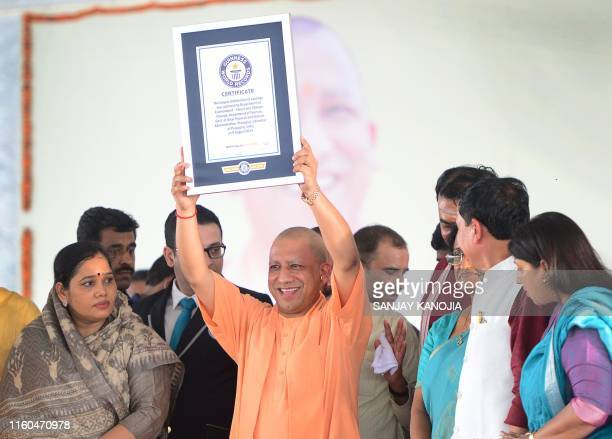 Uttar Pradesh Chief Minister Yogi Adityanath holds a certificate of the Guinness World Records for largest number of sapling distribution at Parade...