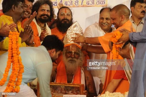 Uttar Pradesh Chief Minister Yogi Adityanath offers silver crown to Mahant Nritya Gopal Das during his 79th birthday function on May 31 2017 in...