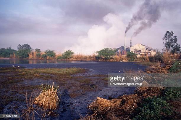 Uttar Pradesh Sugar Cane Sugar mill emitting dark clouds of smoke from chimneys beside polluted lake