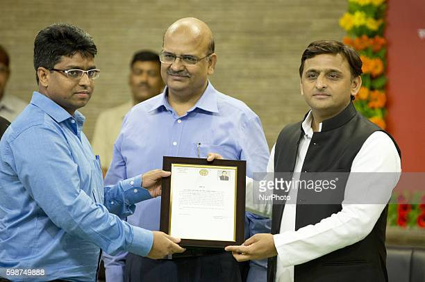 Uttar Pradesh's Chief minister Mr Akhilesh Yadav presents a citations to IAS Ashutosh for his contribution in building Agra Lucknow express way...
