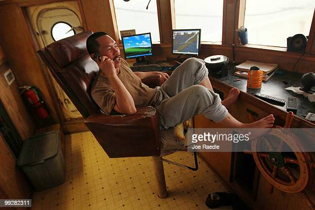 Utvan Cai talks on the cell phone as he passes time away in the shrimp boat he works on after the owner shut down operations due to the massive oil...