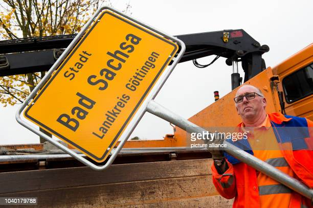 Uwe Aderhold an employee with the Osterode county street building authority holds up a town sign written with 'City Bad Sachsa County Goettingen'...