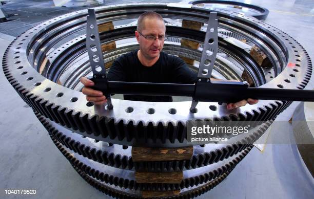 Uwe freilach examines a cog wheel of a slewing bearing at company Hanse Drehverbindungen in Wismar Germany 30 September 2013 The firm signed a...