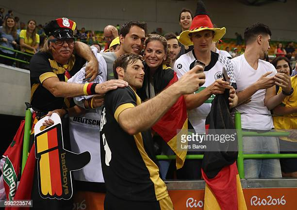 Uwe Gensheimer celebrates victory with fans following the Men's Bronze Medal Match between Poland and Germany on Day 16 of the Rio 2016 Olympic Games...