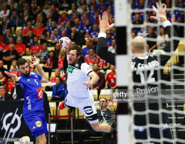 Uwe Gensheimer of Germany is challenged by Nedim Remili of France during the 26th IHF Men's World Championship 3rd place match between Germany and...
