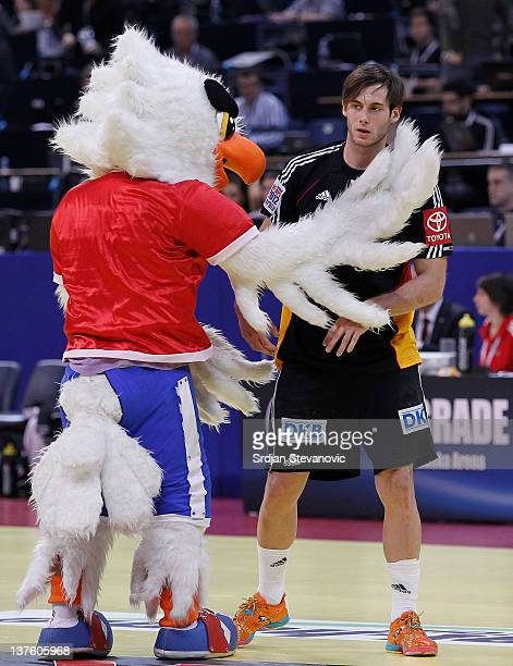 Uwe Gensheimer of Germany looks dejected as he stands beside a mascot after losing the match against Denmark during the Men's European Handball...