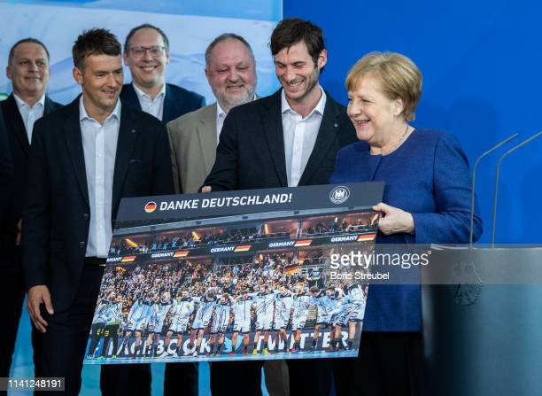 Uwe Gensheimer player of the German national handball team hands a pictures over to Chancellor Angela Merkel at Chancellery on April 08 2019 in...