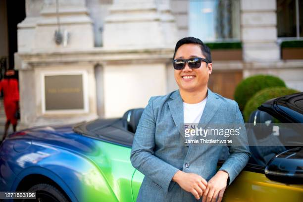 """Uwern Jong poses with the rainbow Bentley during the """"Henpire"""" podcast launch event at Langham Hotel on September 10, 2020 in London, England."""