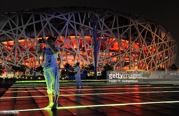Uxia Yu takes a picture of the National Aquatics Center Behind her is the Beijing National Stadium which runs has fountains of water that dances to...