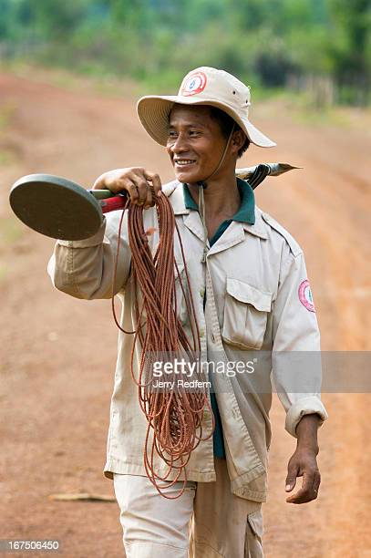 UXOLao technician walks down a new road built atop the old Ho Chi Minh Trail. He spent the day finding buried explosives in a village that recently...