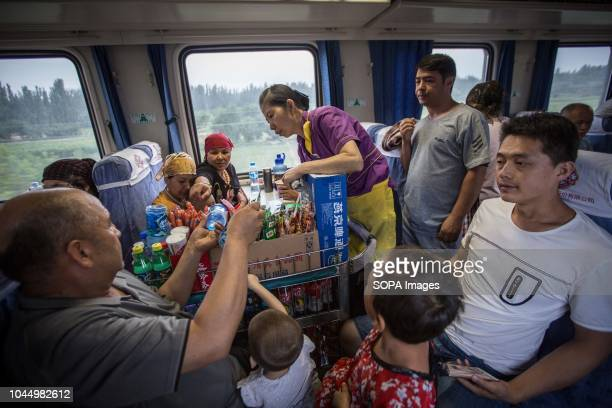 Uyghur and Han Chinese seen buying food at a local vendor inside a train from Hotan to Kashgar in Xinjiang Uyghur Autonomous Region in China Kashgar...