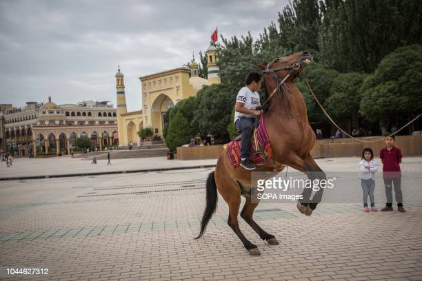 Uyghur boy sit atop of a horse outside the Chinese largest mosque Id Kah in the Kashgar old Town in Kashgar city northwestern Xinjiang Uyghur...