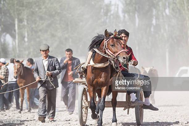 CONTENT] Uyghur ethnic minority man riding a horse and carriage to show it to possible buyers at Kashgar sunday livestock market Kashgar market is a...