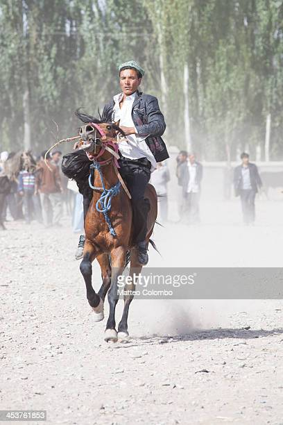 CONTENT] Uyghur ethnic minority man riding a horse to show it to possible buyers at dusty Kashgar sunday livestock market Kashgar market is a famous...