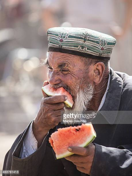 Uyghur ethnic minority old man wearing traditional hat and eating a watermelon at Kashgar sunday livestock market in the autonomous chinese region of...