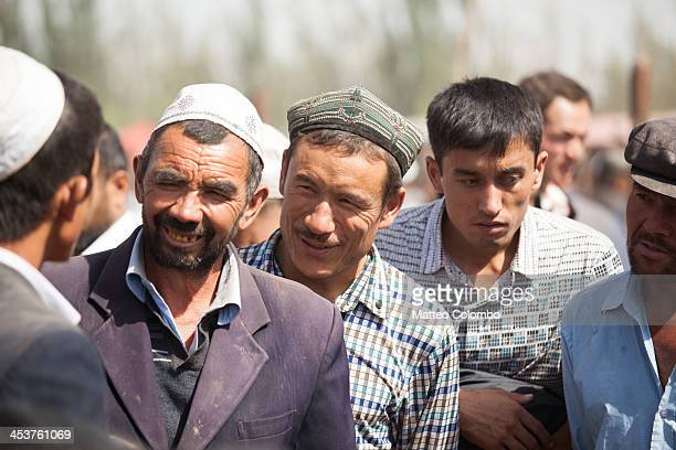 CONTENT] Uyghur ethnic minority people discussing about the sale of livestock at Kashgar sunday livestock market in the autonomous chinese region of...