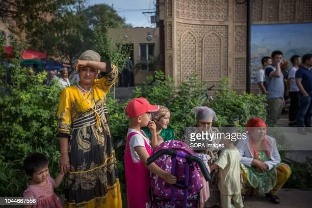 Uyghur families seen watching the Uyghur dancing show in the streets of Kashgar, northwestern Xinjiang Uyghur Autonomous Region in China. Kashgar is...