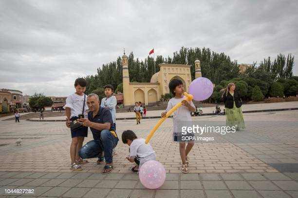 Uyghur family is pictured front of the most famous Kashgar mosque 'Id Kah', build by Saqsiz Mirza in 1442 and knows as the biggest Chinese mosque, in...