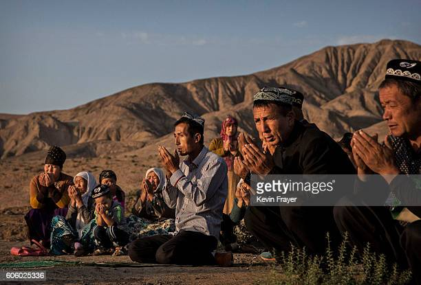 A Uyghur family pray at the grave of a loved one on the morning of the Corban Festival on September 12 2016 at a local shrine and cemetery in Turpan...