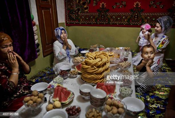 Uyghur family pray before lunch on the Eid holiday on July 29 2014 in old Kashgar Xinjiang Uyghur Autonomous Region China Nearly 100 people have been...
