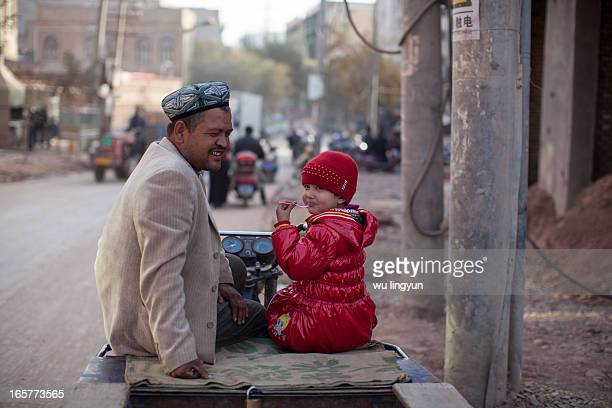 CONTENT] Uyghur girl was eating ice cream with her father on her father's motor tricycle in street of Kashi