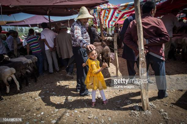 Uyghur little girl walks through the crowd at a livestock market in Kashgar city northwestern Xinjiang Uyghur Autonomous Region in China The Kashgar...
