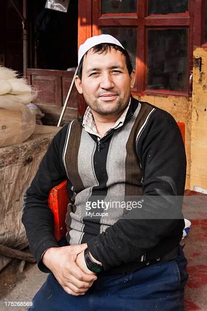 Uyghur man portrait with hat at bazaar. Kashgar, Xinjiang, China
