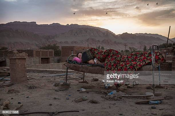 A Uyghur man sleeps outside on the rood of his house due to high temperatures before the Corban Festival on September 10 2016 in Turpan County in the...