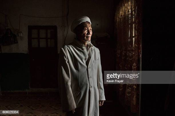 A Uyghur man stands in the doorway of his house after visitors left after a holiday meal during the Corban Festival on September 13 2016 in Turpan...
