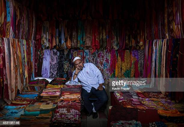 Uyghur man waits for customers at his headscarf shop at a local market on August 2 2014 in Kashgar Xinjiang Uyghur Autonomous Region China Nearly 100...