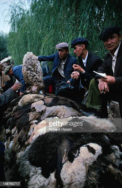 uyghur men from kashgar sell goat skins at the sunday market - men stockfoto's en -beelden