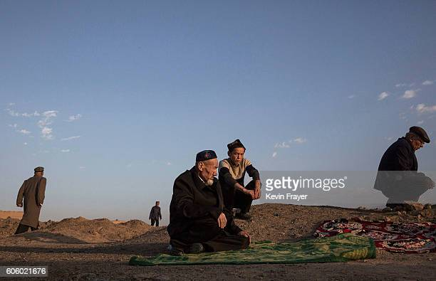 Uyghur men gather to pray at the grave of a loved one on the morning of the Corban Festival on September 12 2016 at a local shrine and cemetery in...
