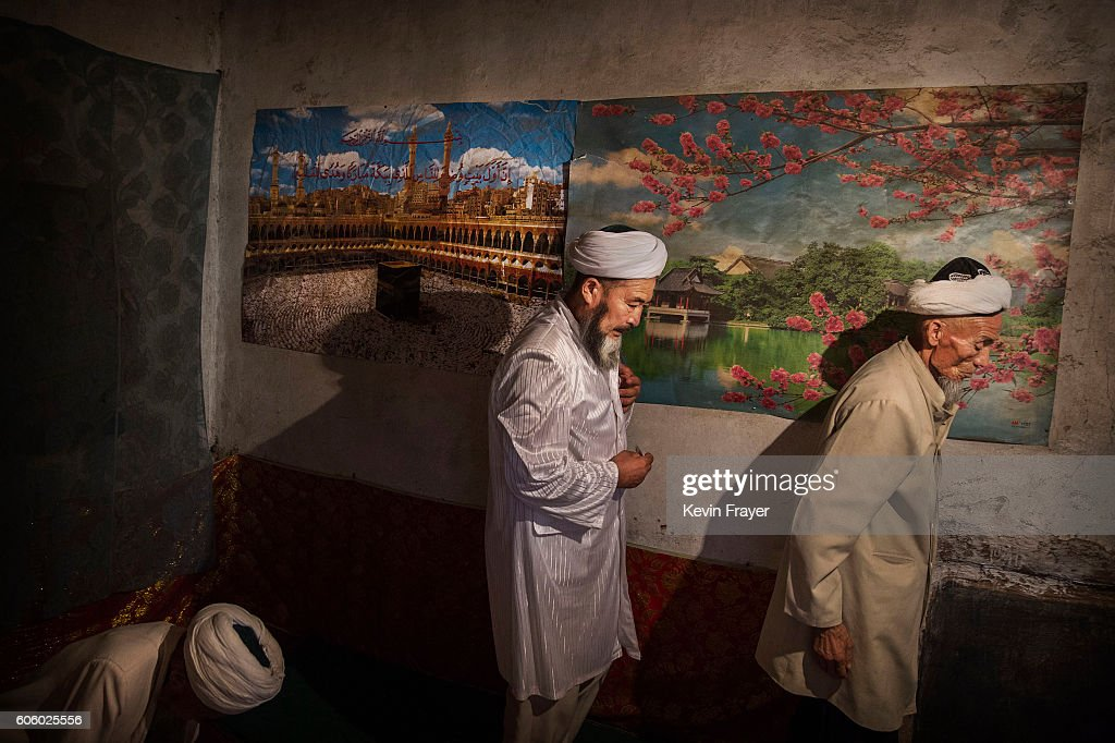 Uyghur men pass a poster showing Mecca as they leave following a holiday meal during the Corban Festival on September 13, 2016 in Turpan County, in the far western Xinjiang province, China. The Corban festival, known to Muslims worldwide as Eid al-Adha or 'feast of the sacrifice', is celebrated by ethnic Uyghurs across Xinjiang, the far-western region of China bordering Central Asia that is home to roughly half of the country's 23 million Muslims. The festival, considered the most important of the year, involves religious rites and visits to the graves of relatives, as well as sharing meals with family. Although Islam is a 'recognized' religion in the constitution of officially atheist China, ethnic Uyghurs are subjected to restrictions on religious and cultural practices that are imposed by China's Communist Party. Ethnic tensions have fueled violence that Chinese authorities point to as justification for the restrictions.