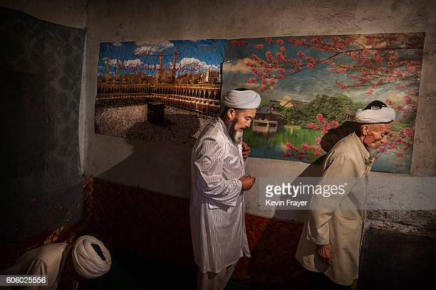 Uyghur men pass a poster showing Mecca as they leave following a holiday meal during the Corban Festival on September 13 2016 in Turpan County in the...