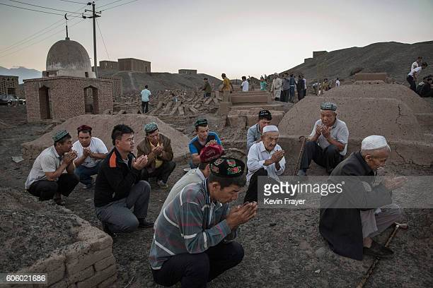 Uyghur men perform prayers for ancestors at a cemetery before the Corban Festival on September 11 2016 in Turpan County in the far western Xinjiang...