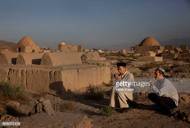 A Uyghur men pray at the grave of a loved one on the morning of the Corban Festival on September 12 2016 at a local shrine and cemetery in Turpan...