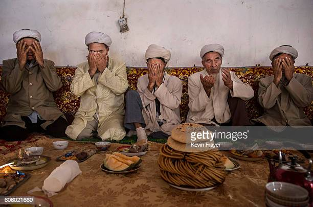 Uyghur men pray before eating a holiday meal during the Corban Festival on September 13 2016 in Turpan County in the far western Xinjiang province...