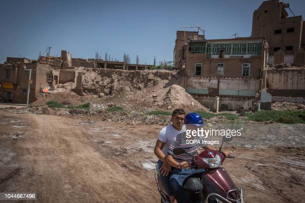 Uyghur men seen riding a Chinese branded electric scooter through rubbles of traditional houses set to be completely demolish to make way for new...