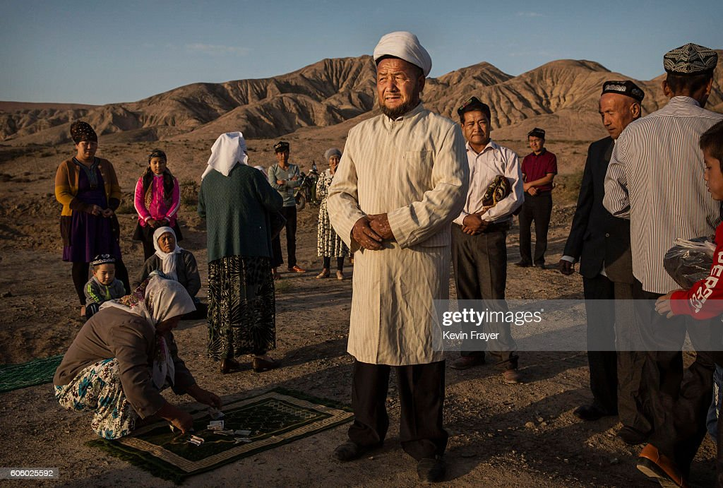 A Uyghur Muslim Imam, center, gathers with a family before prayers at the grave of a loved one on the morning of the Corban Festival on September 12, 2016 at a local shrine and cemetery in Turpan County, in the far western Xinjiang province, China. The Corban festival, known to Muslims worldwide as Eid al-Adha or 'feast of the sacrifice', is celebrated by ethnic Uyghurs across Xinjiang, the far-western region of China bordering Central Asia that is home to roughly half of the country's 23 million Muslims. The festival, considered the most important of the year, involves religious rites and visits to the graves of relatives, as well as sharing meals with family. Although Islam is a 'recognized' religion in the constitution of officially atheist China, ethnic Uyghurs are subjected to restrictions on religious and cultural practices that are imposed by China's Communist Party. Ethnic tensions have fueled violence that Chinese authorities point to as justification for the restrictions.
