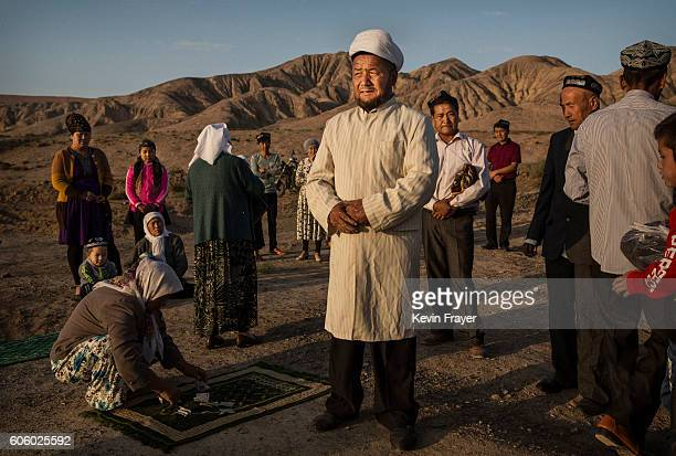 A Uyghur Muslim Imam center gathers with a family before prayers at the grave of a loved one on the morning of the Corban Festival on September 12...