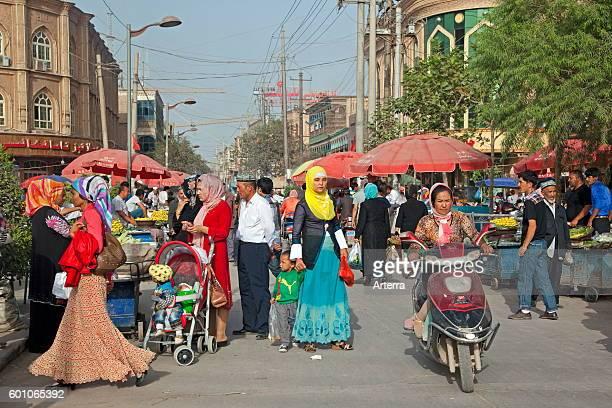 Uyghur Muslim women wearing Islamic dress in shopping street in the city Kashgar / Kashi Xinjiang China