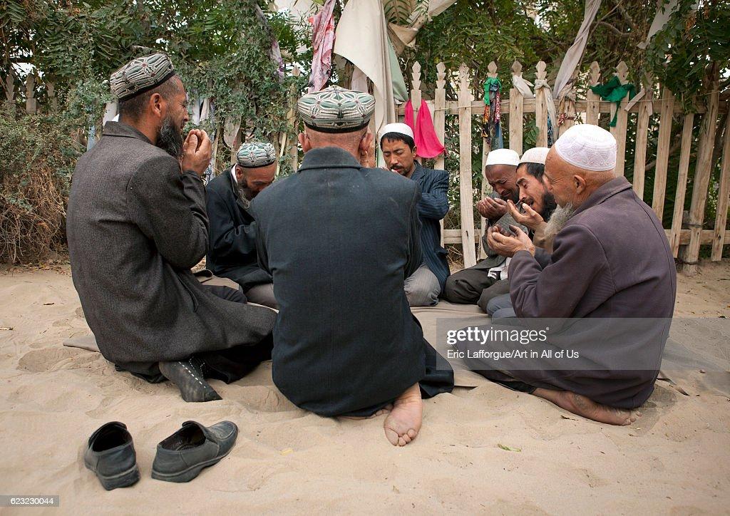 Uyghur sufi man praying at imam Asim tomb in the Taklamakan desert, Xinjiang Uyghur Autonomous Region, China... : News Photo