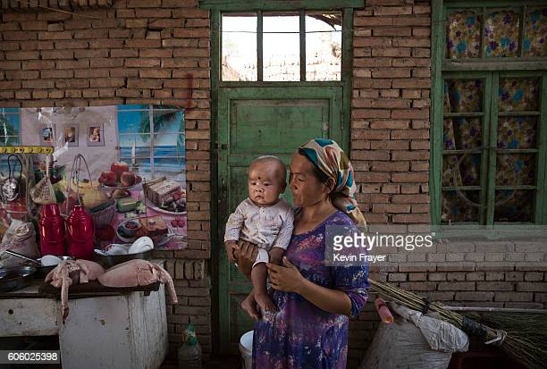 A Uyghur woman holds a child in her home as they prepare food during the Corban Festival on September 12 2016 in Turpan County in the far western...