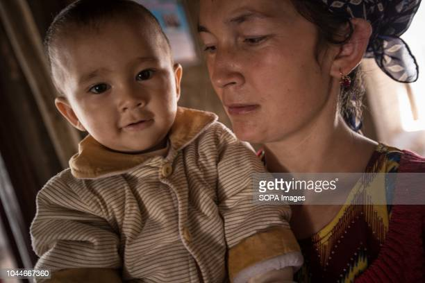 Uyghur woman holds her son outside her house in the Kashgar old town northwestern Xinjiang Uyghur Autonomous Region in China Kashgar is located in...