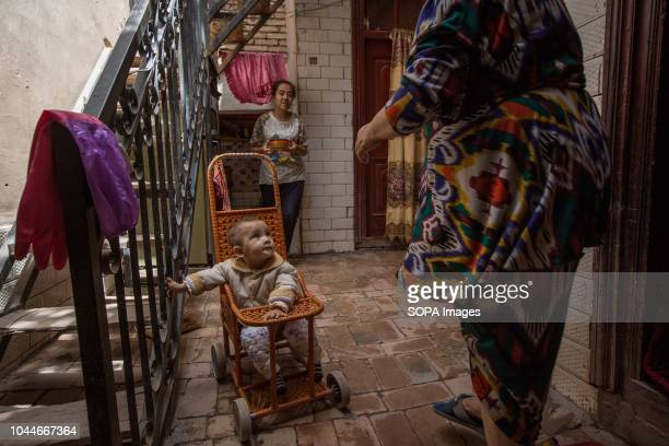 Uyghur woman holds the lunch for her mother inside a traditional house in the Kashgar old town, northwestern Xinjiang Uyghur Autonomous Region in...