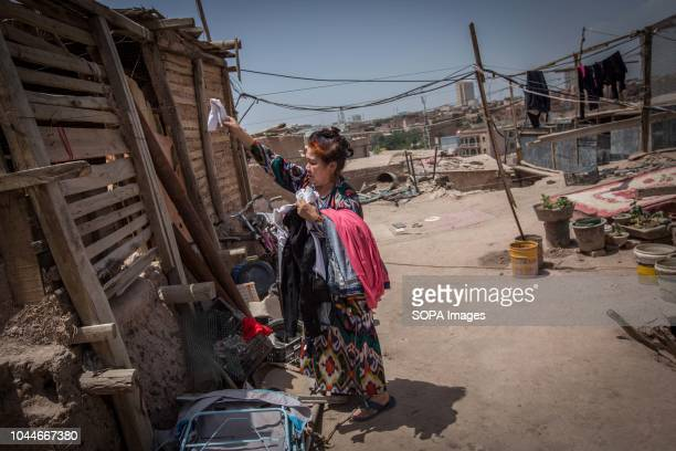 Uyghur woman pick up the dried clothes from the rooftop of her house as the Kashgar old town can be seen in Kashgar city northwestern Xinjiang Uyghur...