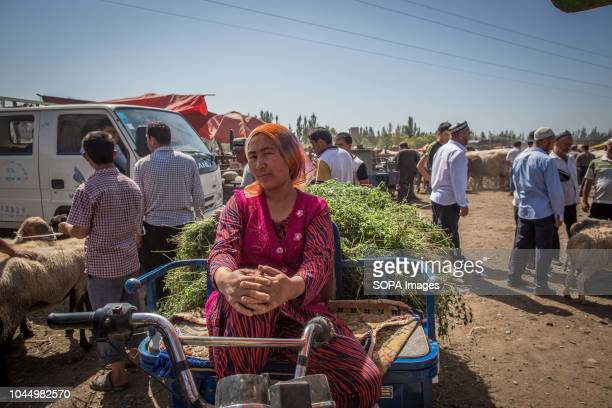 Uyghur woman waits for customers at a livestock market in Kashgar city northwestern Xinjiang Uyghur Autonomous Region in China The Kashgar Livestock...
