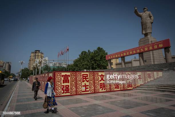 Uyghur woman walks pass a statue of Mao Zedong in the People's Park in Kashgar city northwestern Xinjiang Uyghur Autonomous Region in China Kashgar...